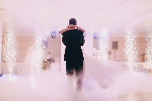 Rear view of just-married couple dancing