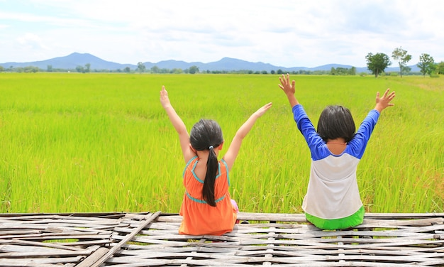 Rear view of little asian children stretch arms and relaxed sitting on bamboo litter at the young green paddy fields with mountain and cloud sky.
