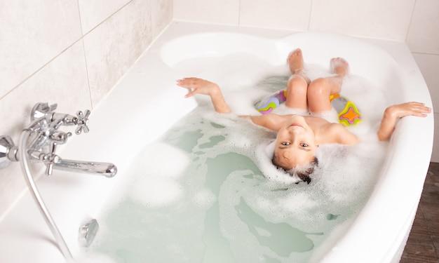 背面図小さな女の子が泡とゴムリング付きの浴槽で入浴します