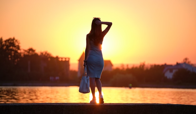 Rear view of lonely woman standing alone on lake shore on warm evening. solitude and relaxing in nature concept.