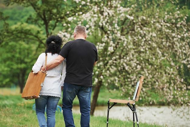 배면도. 사랑스러운 성숙한 부부는 여가 시간에 공원에서 산책을