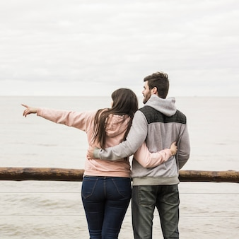 Rear view of loving young couple overlooking sea