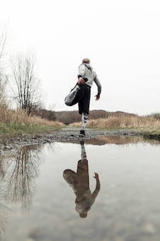 Rear view of male athlete exercising near the puddle