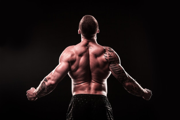 Rear view. male bodybuilder looking at copy space.isolated on black background