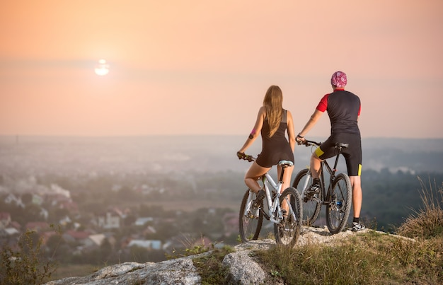 Rear view male and female bikers with moutains bicycles standing on the top of a hill