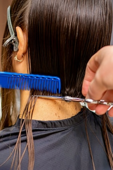 Rear view of a male hairdresser cuts hair of young woman with siscors and comb