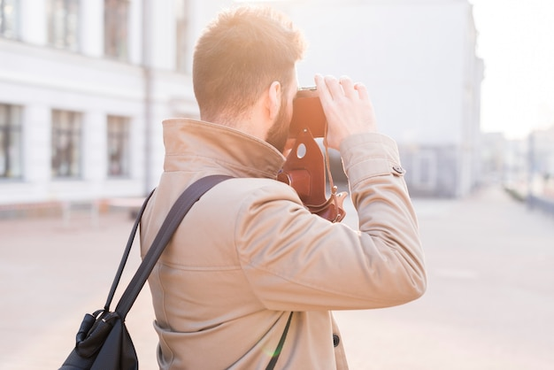 Rear view of a male traveler taking the picture in the city with camera