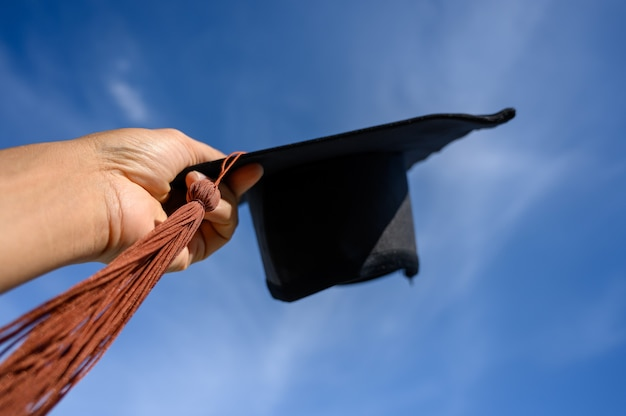 Rear view of a male university graduate stands and holds black hat of graduates in the sky.