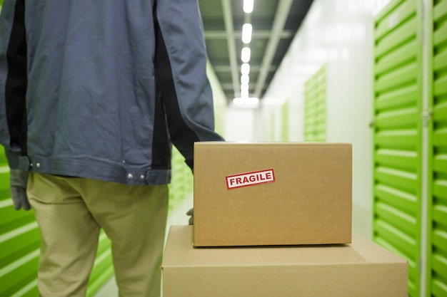 Rear view of man carrying cardboard boxes on trolley in the warehouse