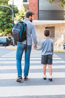 Rear view of a man carrying school bag walking on crosswalk with his son