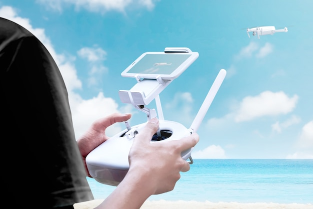Rear view of man controlling white drone which flying over the beach with blue ocean