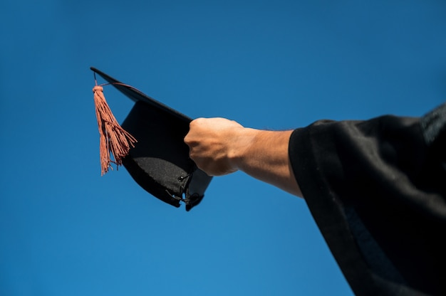 Rear view of man in graduation gown holding cap standing against sky