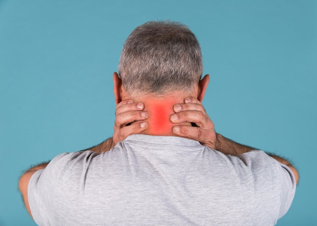 Rear view of a man having severe neck pain