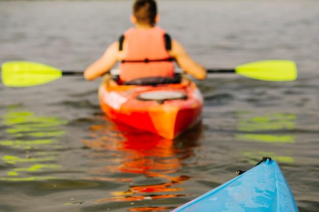 Rear view of man kayaking