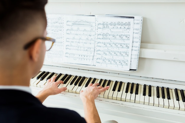 Rear view of man looking at musical sheet playing piano