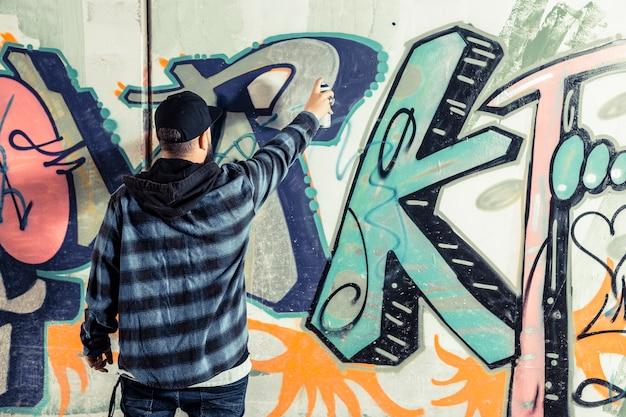 Rear view of a man making graffiti on wall