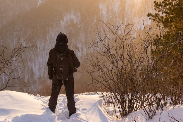 Rear view of a man on a mountain looking into the distance in the rays of the setting sun. hiking in the mountains