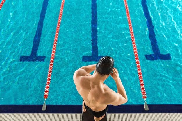 Retrovisione di un uomo che prepara gli occhiali di protezione di nuoto