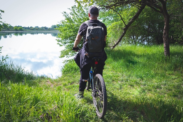Rear view of a man riding a bicycle on a background of green grass and lake
