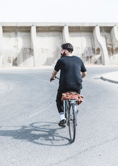 Rear view of a man riding the bicycle on road