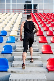 Rear view of a man running up stairs on the bleacher