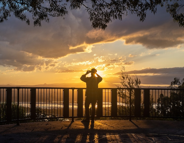 オーストラリア、ヌーサの日没時間に展望台で写真聖霊降臨祭の電話を撮る男のシルエットの背面図