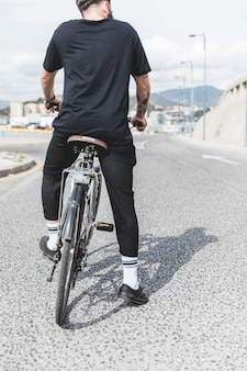 Rear view of man sitting on bicycle over the straight road