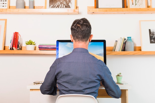 Rear view of man sitting on chair using computer in office