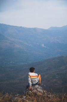 Vista posteriore di un uomo seduto su una roccia contemplando la natura.