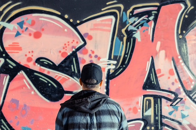 Rear view of a man standing in front of graffiti