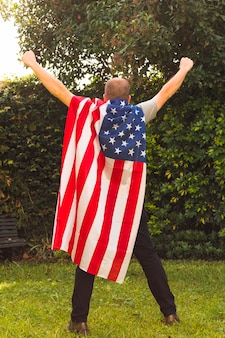 Rear view of a man standing in park wearing usa flag cape raising his arms
