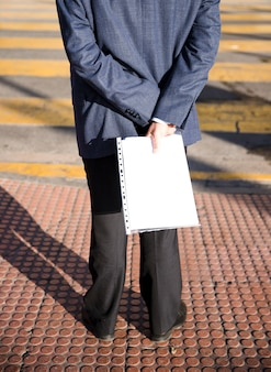 Rear view of a man standing on sidewalk holding white folder in hand