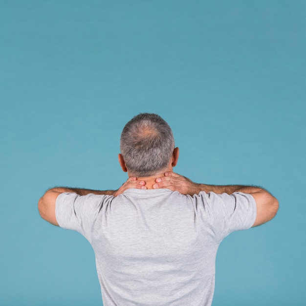Rear view of man suffering from neck pain over blue backdrop