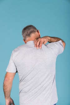 Rear view of a man suffering from neck pain in front of blue backdrop