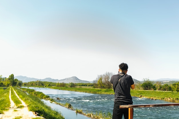 Rear view of man taking picture of flowing river