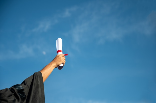 Rear view of man throwing hands up a certificate and cap in the air, graduation day on sky background Premium Photo