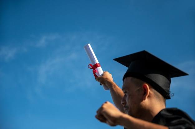 Rear view of man throwing hands up a certificate and cap in the air, graduation day on sky background