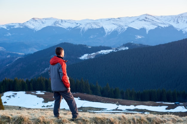 Rear view of man tourist enjoying beautiful panorama in the evening on snow-covered mountains
