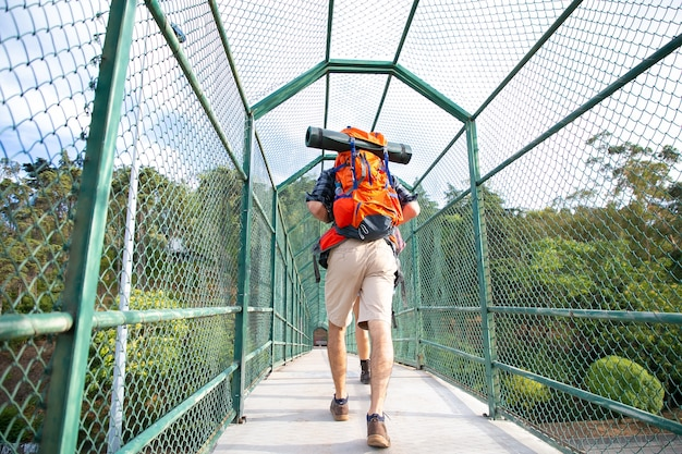 Rear view of man walking on bridge surrounded with green grid. hikers carrying backpacks, crossing river or lake through pathway.  backpacking tourism, adventure and summer vacations