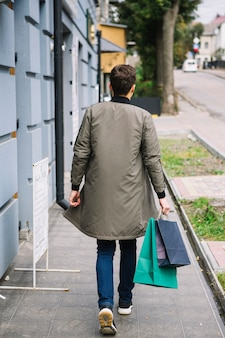 Rear view of a man walking on sidewalk holding shopping bags