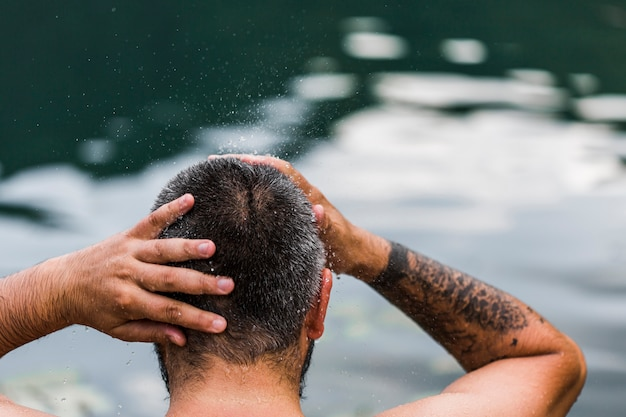 Rear view of a man washing his hair in front of lake