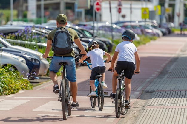 Rear view of a man with children riding bikes on a bicycle path in the city, sunny day