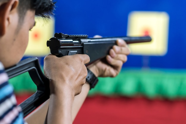 Rear view of man with his gun on shooting at the target in practice shooting