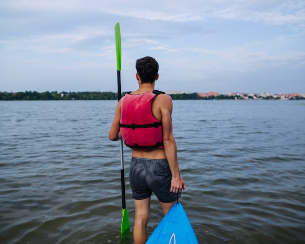Rear view of man with oar and kayak near the lake shore