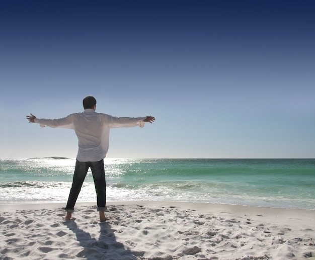 Rear view of man with open arms facing the sea