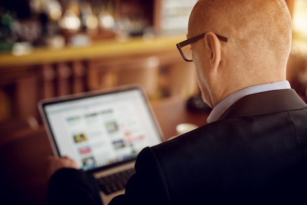 Rear view of mature elegant businessman using the laptop while sitting at the table of the coffee shop.