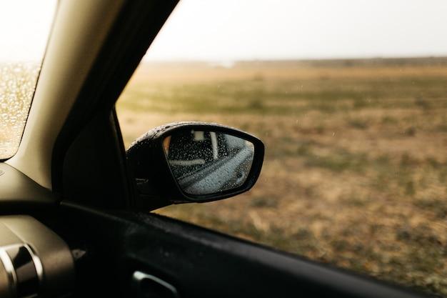 Rear view mirror seen through the glass. wet car window. close up rain drop. car view see the mirror.