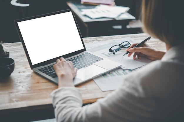 Макет изображения руки женщины, работающей на ноутбуке с пустым белым экраном на рабочем столе, копией пространства сзади