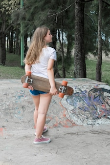 Rear view of modern girl holding skateboard standing in park
