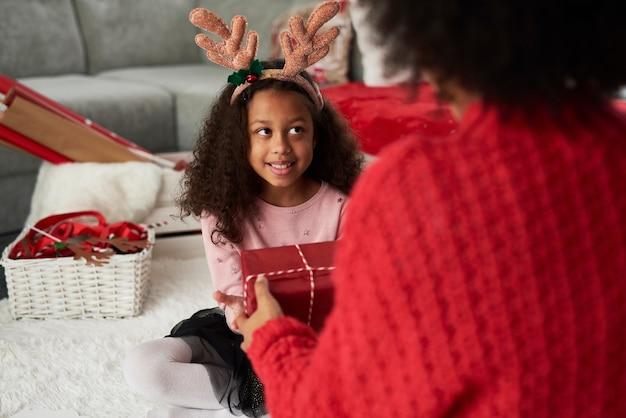 Retrovisione della mamma che dà a sua figlia il regalo di natale